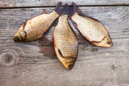 fish tail: Several carp fishes on wooden surface Stock Photo