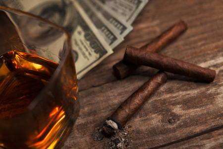 Cigarettes, glass with brandy on the table and money in the background