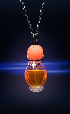 Love potion in small bottle hanging on chains on dark background