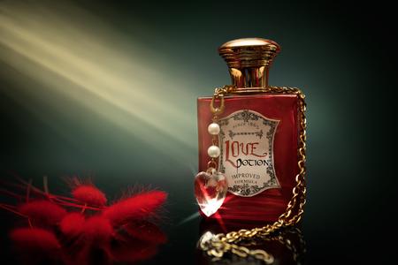 elixir: Poción de amor roja en una botella con cadenas y corazón de cristal alrededor de la botella Foto de archivo