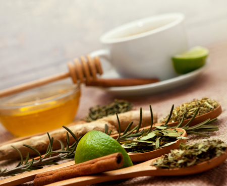 Spoons with tea herbs, lime and honey on the table Stock Photo