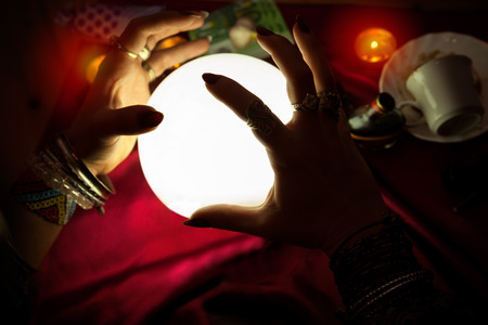 esoterism: Hands of gypsy fortune teller woman above illuminated crystal ball