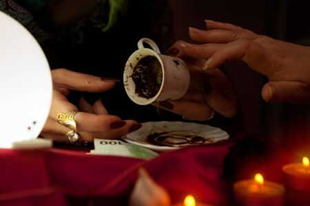 esoterism: Old gypsy fortune teller holds a coffee cup for fortune telling Stock Photo