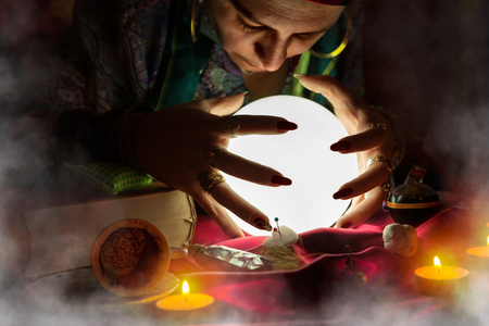 psychic reading: Gypsy woman fortune teller looking at shining crystal ball