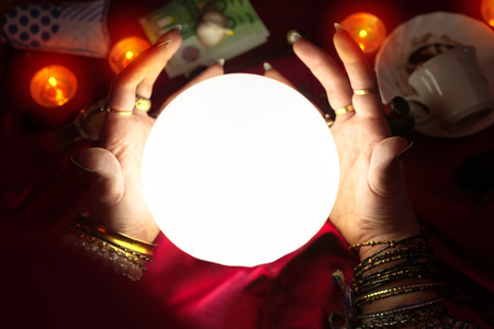 Gypsy woman fortune teller put her hands around illuminated crystal ball