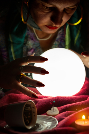 Glowing crystal ball for fortune telling and hands of gypsy fortune teller