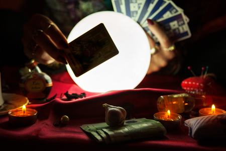 Tarot card in hand of fortune teller with crystal ball in the background