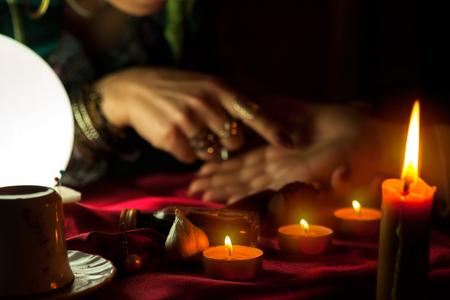 Vlam van brandende kaarsen en vrouw die de toekomst van palm op de achtergrond leest Stockfoto