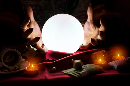 Hands of fortune teller with illuminated crystal ball in the middle