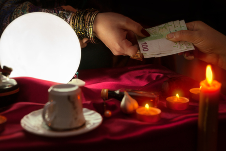 Woman fortune teller receive money for fortune telling
