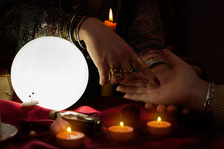 Gypsy woman fortune teller read a fortune from palm Stock Photo