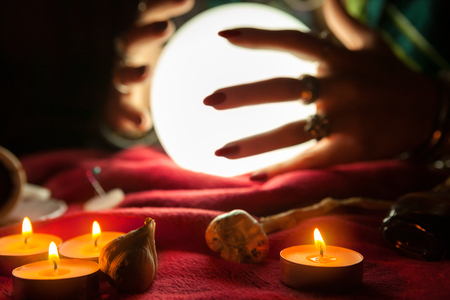 esoterism: Hands of fortune teller witch in front of illuminated crystal ball