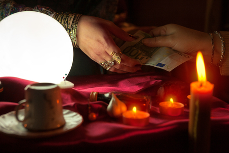 Old fortune teller woman receive money for fortune telling