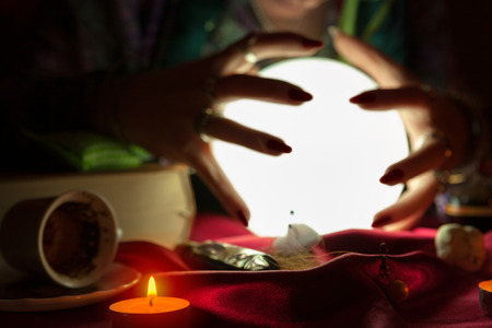 Hands of fortune teller woman around glowing crystal ball Stock Photo