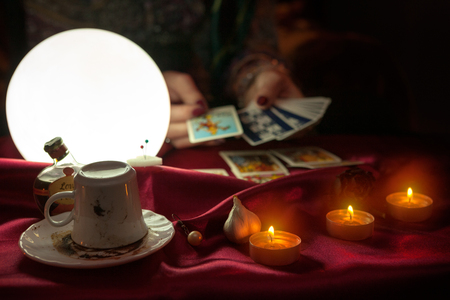 Cofee cup, candles and shiny crystal ball with tarot card in hand of fortune teller woman in the background