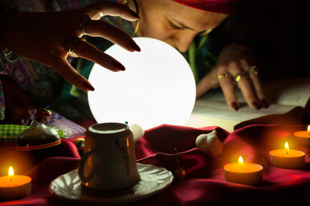 Old gypsy fortune teller woman looking and reading the spells from the book