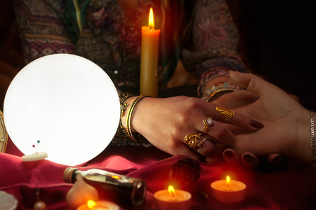 Gypsy woman fortune teller reading the future from womans hand Stock Photo