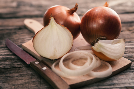 Fresh uncooked onion and onion cuts on chopping board with a kitchen knife