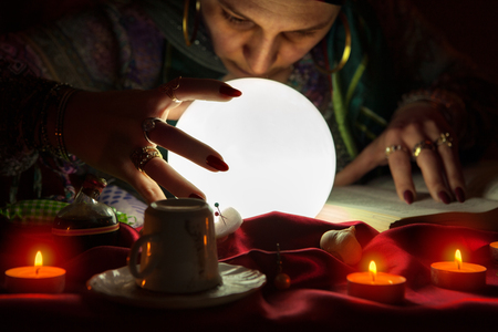 Gypsy fortuneteller gazes into crystalball,using sorcery and voodoo