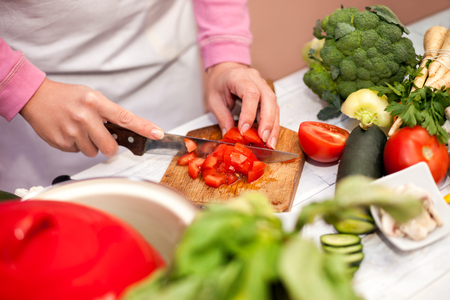 Cutting tomato with knife, preparing vegetable for salad on chopping board Stock Photo