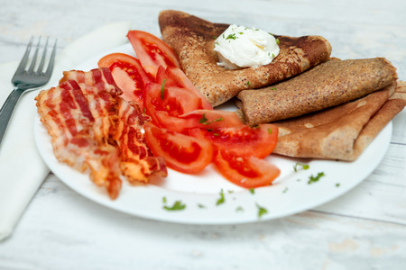 Breakfast with pancakes, tomato and bacon on a plate Stock Photo