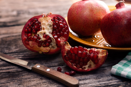 Red tasty pomegranate cut in half with knife