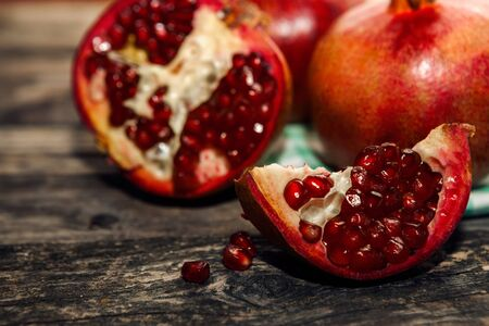 Sliced piece of fresh pomegranate with second half in the background Stock Photo