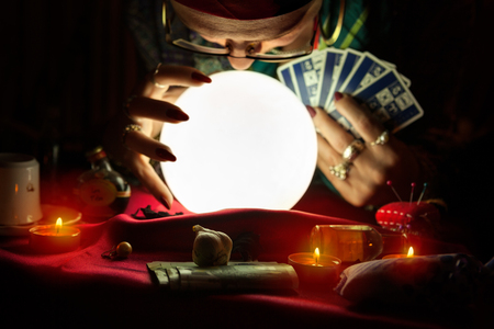 Old gypsy woman looking at crystal ball and holding a tarot cards