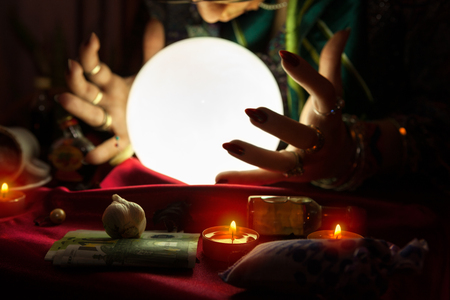 Illuminated crystal ball and hands of gypsy fortune teller woman Stock Photo