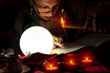 Woman fortuneteller holding candle and black rose for sorcery