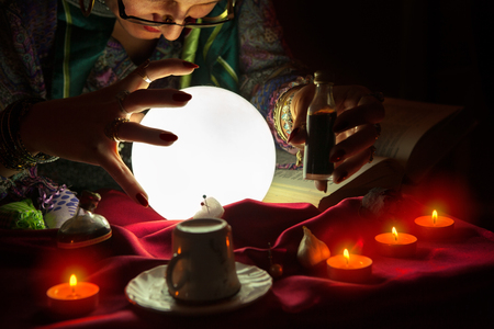 Fortune teller woman staring at crystal ball,potion and witchcraft Stock Photo