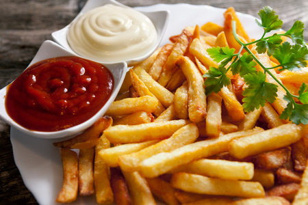 Close up of french fires on a plate with parsley, tomato sauce and mayonnaise