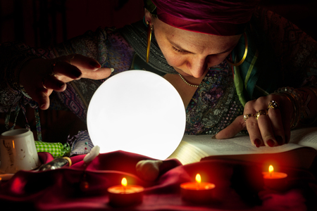 Old gypsy woman read an old book of spells and holds a hand above crystal ball Stock Photo