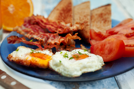 Fried eggs,tomatoes and crispy bacon-breakfast on plate