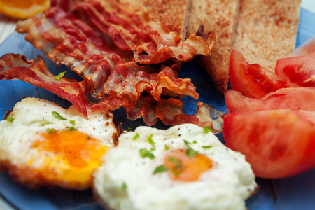 Close shot of breakfast with fried eggs, bacon and tomato on a plate