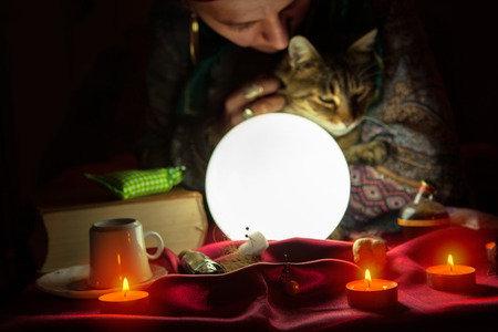 Woman fortuneteller during session with crystal ball and cat
