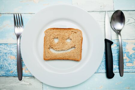 Toast with a smile on plate with cutlery, breakfast idea Stock Photo