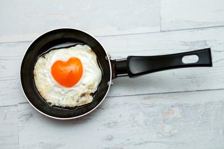 Fried egg in shape of heart in a pan,romantic breakfast