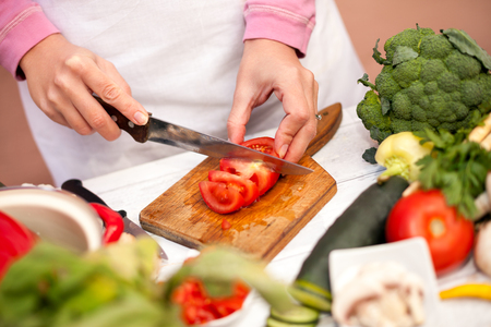 Woman cutting tomato on slices and preparing it for salad on chopping board Stock Photo