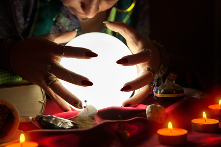 Old gypsy fortune teller with crystal ball predicting the future