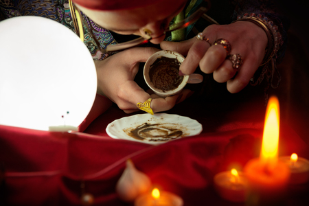 esoterism: Woman fortune teller looking in empty coffee cup and reads future Stock Photo
