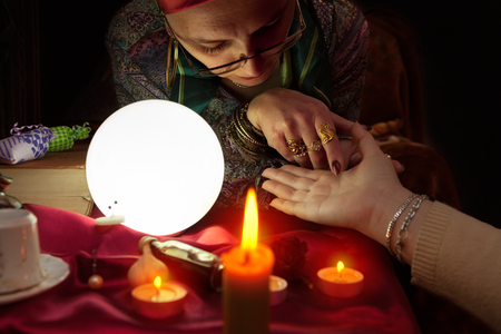 Old fortune teller woman holding another woman hand for palm reading