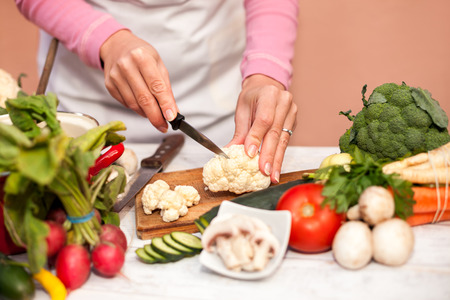 Woman cutting fresh cauliflower with a knife on chopping board
