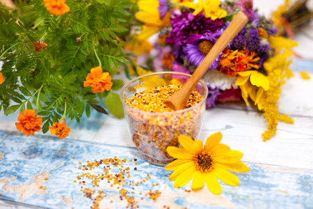 bee on flower: Pollen in glass with wooden spoon on the table