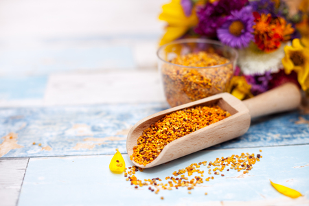 bee on flower: Wooden scoop with bee pollen on the table, plastic glass with pollen and flower in the background
