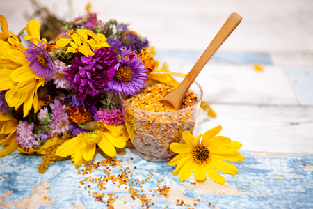 bee on flower: Wooden spoon in glass with pollen on the table