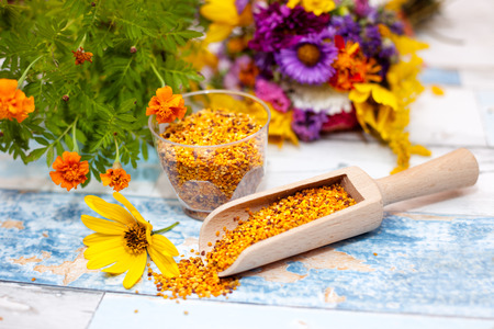 bee on flower: Wooden scoop with bee pollen, pollen in plastic glass with yellow flower on the table Stock Photo