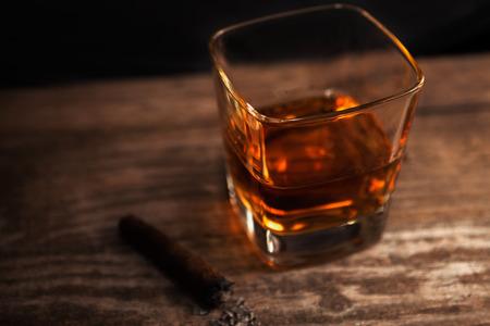 Vaso con whisky y cigarro con cenizas sobre la mesa