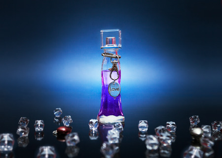 elixir: Purple love potion in a bottle with metal love tag around the bottle and crystals on dark background