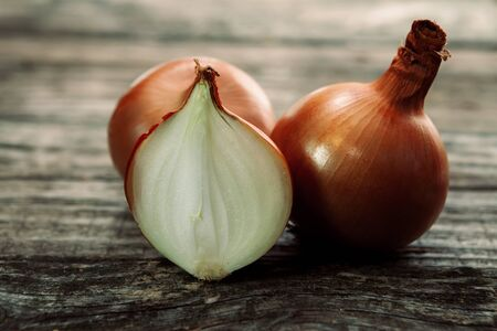 Fresh bulbs of onion on wooden background Stock Photo
